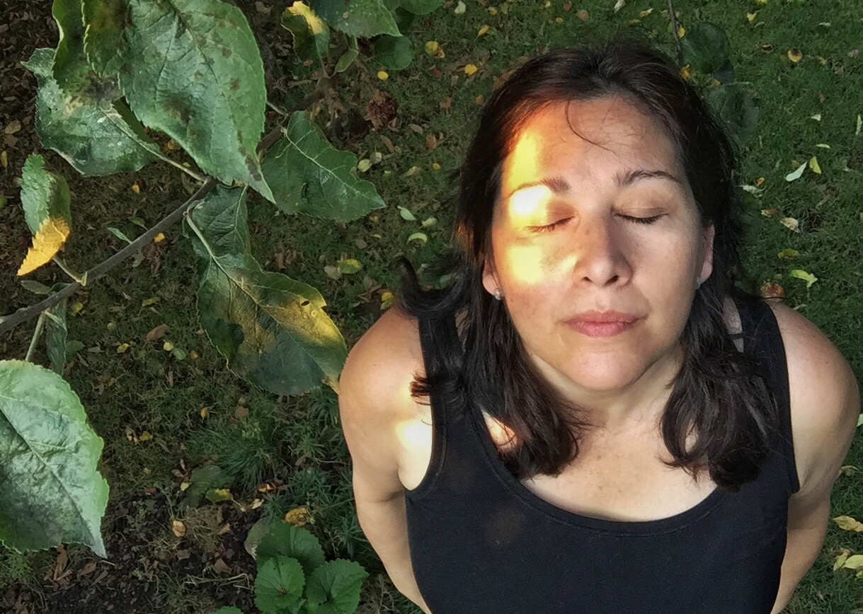 emmy in garden with sun on face and eyes closed