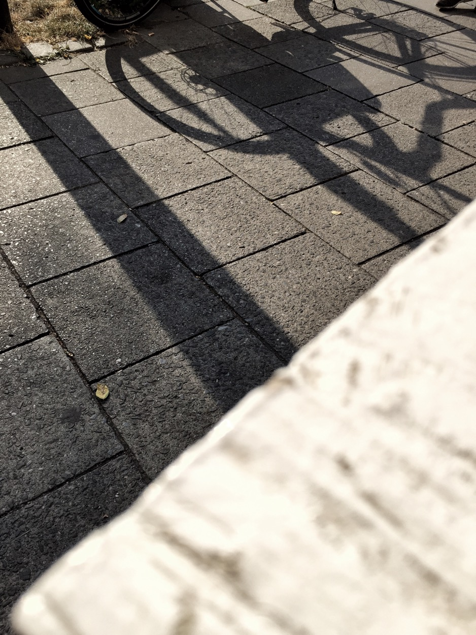 shadows near my cafe table which include a bike.